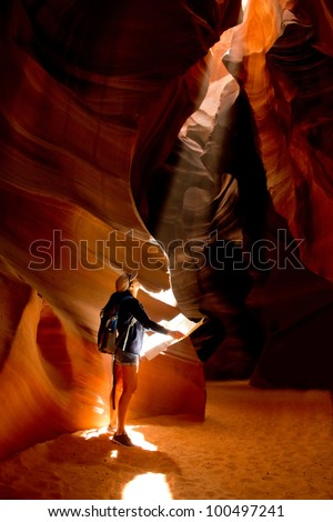 Woman exploring inside a cave at the Grand Canyon - stock photo