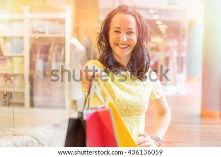 Woman extending hand with shopping bags