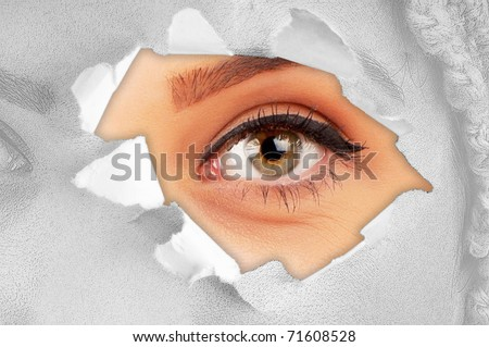 Woman eye through hole in paper - stock photo