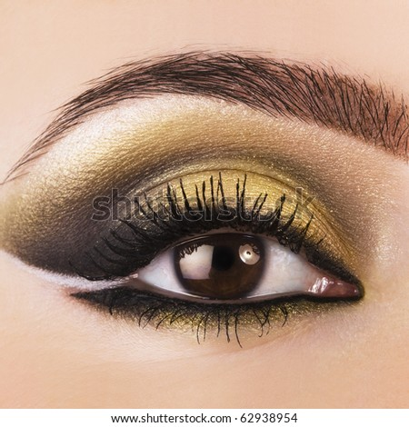 Woman eye with beautiful golden makeup - stock photo