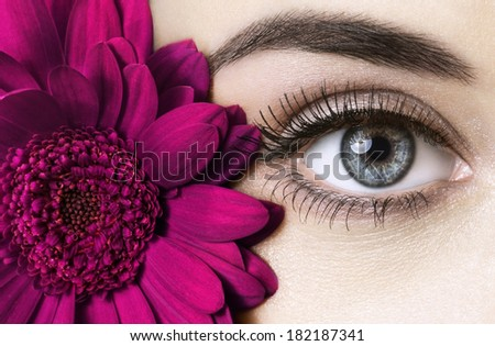 woman eye with beautiful makeup and purple flower  - stock photo