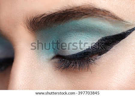 Woman eye with beautiful turquoise smokey eyes