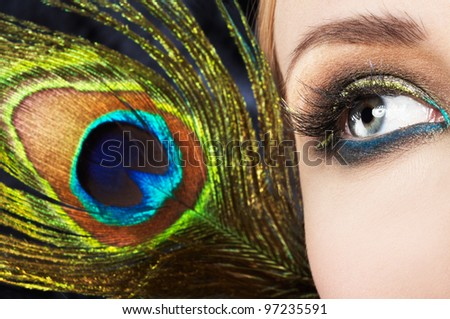 Woman eye with colorful makeup and peacock feather - stock photo