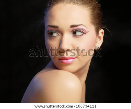 Woman eye with exotic style makeup, isolated on black background