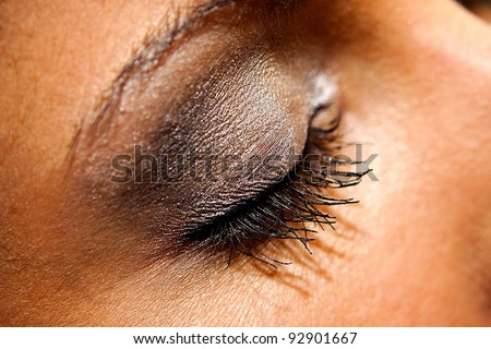 Woman eye with extremely long eyelashes and golden makeup - stock photo