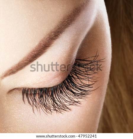 Woman eye with extremely long eyelashes without makeup. - stock photo