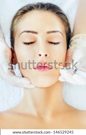 Woman face and beautician hand with syringe - stock photo