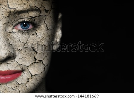Woman face covered with cracked earth texture - symbol of nature disaster or skin care - stock photo