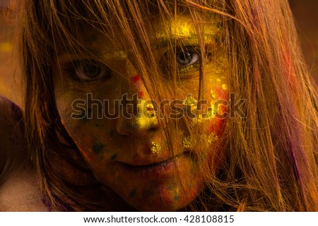 woman face in the colors of Holi closeup