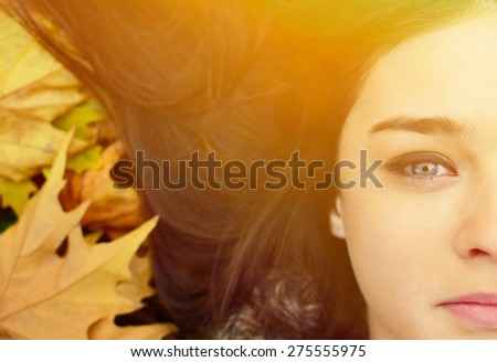 Woman face lying on autumn leaves
