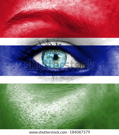 Woman face painted with flag of Gambia - stock photo