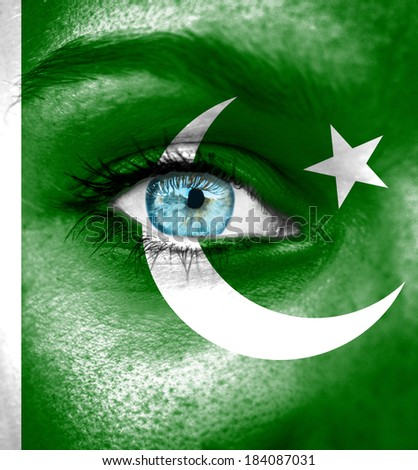 Woman face painted with flag of Pakistan - stock photo