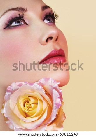 Woman face with beautiful makeup and tender rose - stock photo