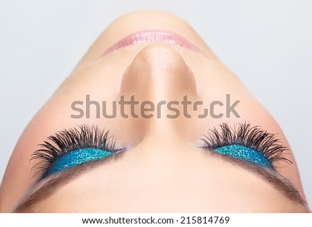 Woman face with blue shining eye make-up  - stock photo