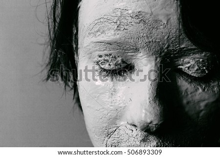 Woman face with cracked skin. Skin of woman is white painted and cracked. Close up. Black and white.
