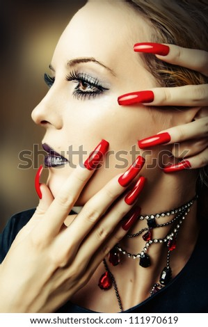 Woman face with fashion make up, false lashes and long red finger nails - stock photo
