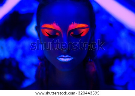 Woman face with fluorescent make up art. Blue background. Studio shot. Orange, pink, blue neon paints. Creative idea is good for clubs, disco, go-go, show concerts, parties. Sexy girl alien cosmo new - stock photo