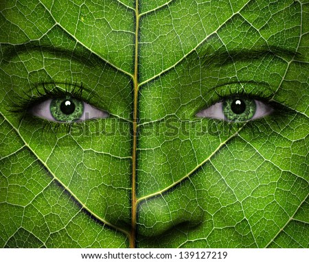 Woman face with leaf texture and green eyes. Ecology concept. - stock photo