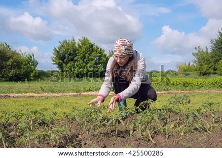 Woman farmer working in the field and reflects about the results of the work. - stock photo