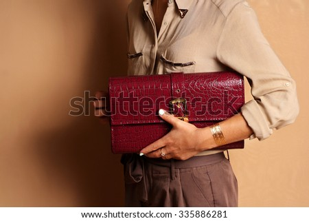 Woman fashionable girl wearing silk blouse holding red leather bag handbag in hand. Stylish accessories - stock photo