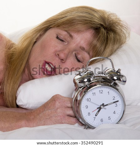 Woman fast asleep with alarm clock