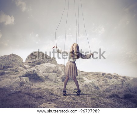 Woman fastened to ropes as a puppet - stock photo