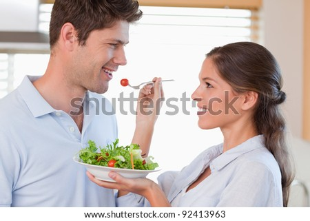 Woman feeding her husband in their kitchen - stock photo