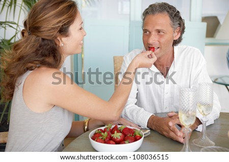 Woman feeding man strawberries while sitting on an outdoors table at home.