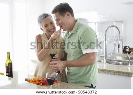 Woman feeding pepper to husband in kitchen - stock photo