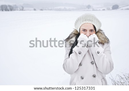 woman feeling cold in field covered in snow with copy space - stock photo