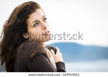 Woman feeling sad and shivering on fresh autumn day. Nostalgic and emotional natural female hugging herself on cold late summer or autumn day.