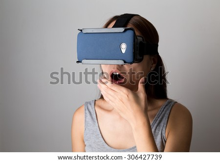 Woman feeling shocking when using the virtual reality device - stock photo