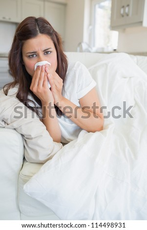 Woman feeling sick and lying on the sofa