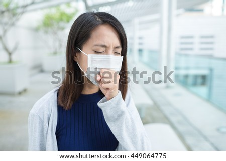 Woman feeling sick and wearing face mask - stock photo