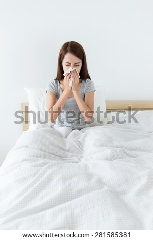 Woman feeling unwell and runny nose at bedroom