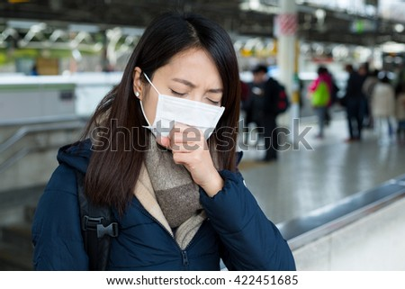Woman feeling unwell and wearing face mask in train station - stock photo