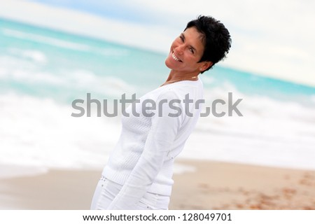 Woman ,feeling wellness,turning and looking back towards camera ocean background.