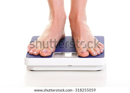 Woman feet and blue weight scale isolated on white background - stock photo