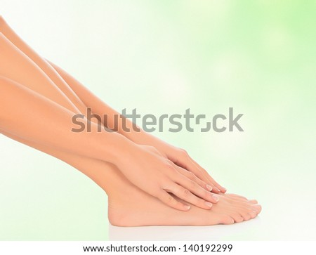woman feet and hands on floor, green blurred background  - stock photo