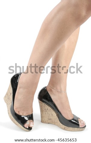 Woman feet and legs with black high heel shoes over white