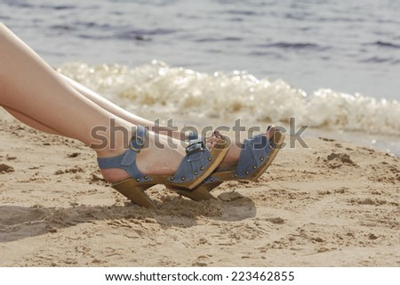 Woman feet in sandals on the beach - stock photo
