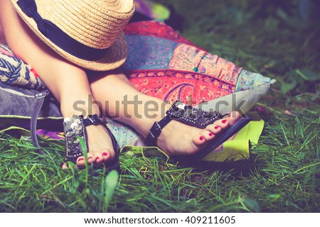 woman feet on grass in flat summer sandals lean on pillows  hat lay on legs  - stock photo