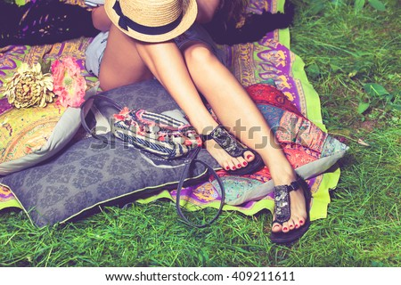 woman feet on grass in flat summer sandals lean on pillows  hat lay on legs from above - stock photo