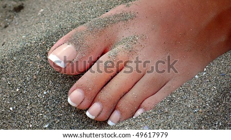 Woman feet on seacoast with a pedicure