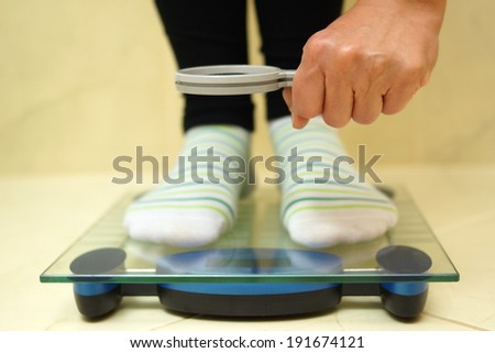 woman feet on weighing scales looking weight over magnifying glass. exaggerate with weight loss concept - stock photo