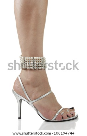 Woman feet wearing silver heel shoes and pearls over white background