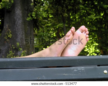 woman feet while resting on a park bench, - stock photo