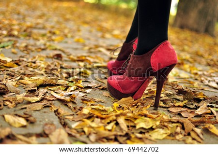 Woman feet  with pink fashion shoes on a late autumn shooting - stock photo