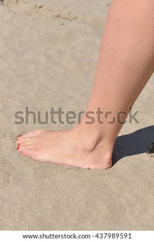 Woman feet with red pedicure walking on the hot sand of the beach. Summer holiday.