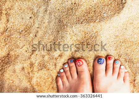 Woman feet with red toenails on natural beach sand